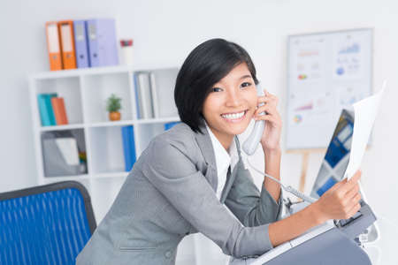 facsimile: Portrait of a cheerful receptionist answering a phone call and looking at camera Stock Photo