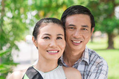 Close-up of a mature couple smiling and looking at camera