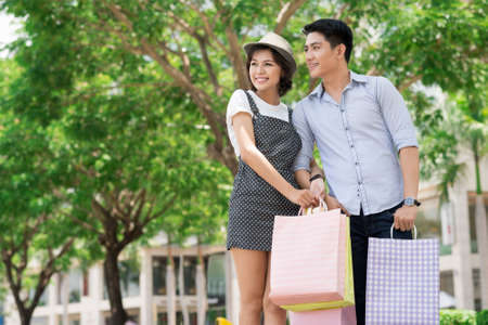 A young couple standing in the park with shopping bags Stock Photo