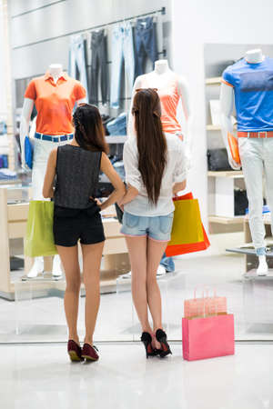 Young ladies with shopping-bags looking at a shop-window viewed back