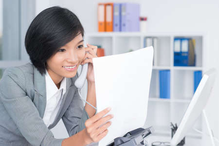 faxing: A secretary making a call after faxing inside Stock Photo