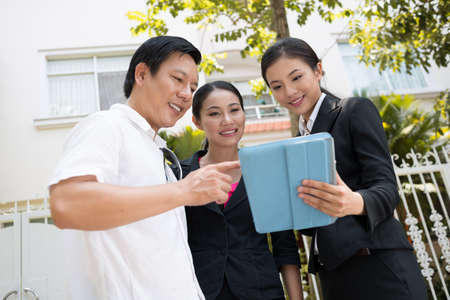 Close-up of a couple and a real estate agent using a tablet outside