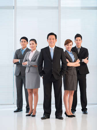 confidently: Full-length portrait of a business team looking confidently at camera