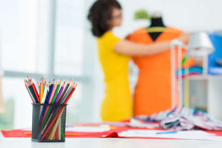 Image of a pencil-holder on the foreground and a dress-maker at work on the background Stock Photo