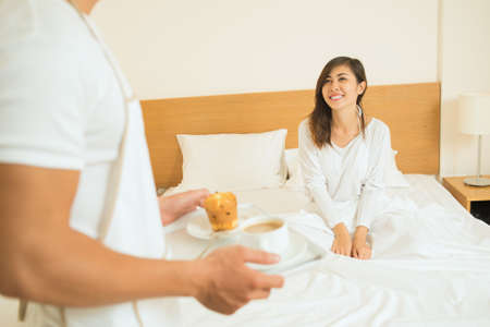 Image of a happy young woman waiting for the breakfast in the bed on the foreground