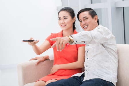 Image of a mid-aged couple with a clicker at home