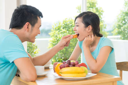 Image of a cheerful couple having breakfast at home