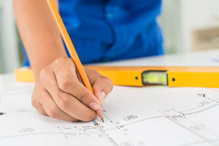 Cropped image of a draftsman correcting a blueprint