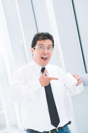 Vertical portrait of a cheerful businessman pointing at his empty teacup