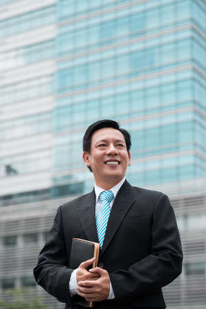 Vertical image of a happy businessman standing in front of the modern building