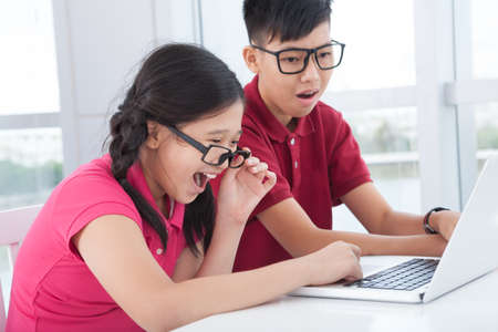 diligent: Image of excited schoolchildren looking in the laptop Stock Photo