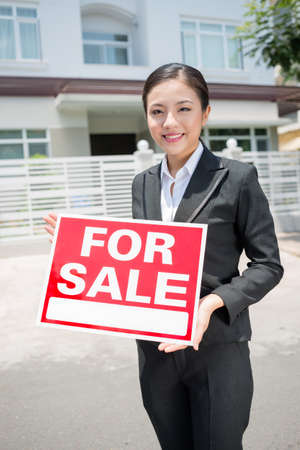 forsale: Vertical portrait of a young real estate agent standing with a placard in hands