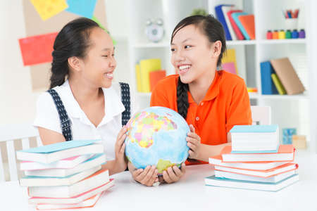 mates: Two school mates holding globe in hands
