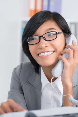 Vertical image of an office worker receiving a phone call