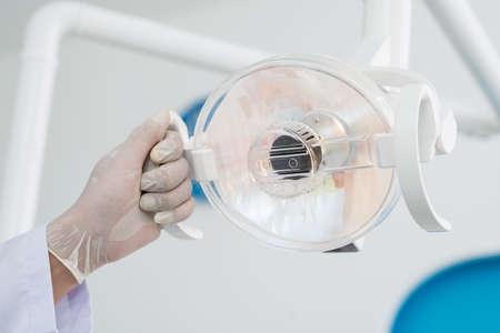 dentalcare: Close-up of male hands holding a dental lamp inside