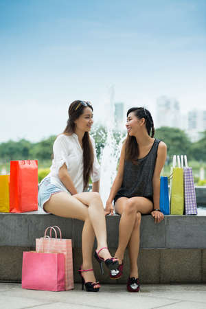 waterworks: Vertical image of two lovely girlfriends talking after shopping on the waterworks outside Stock Photo