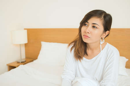 early twenties: Copy-spaced image of a young woman sitting on the bed just after morning awakening Stock Photo
