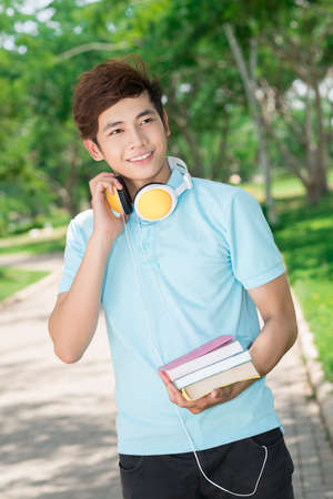 cool guy: Vertical image of a cool guy with textbooks and headphones in hands