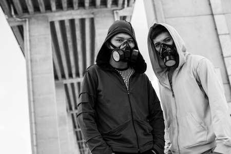 gasmask: Black and white portrait of young guys standing in gas-masks and looking at camera