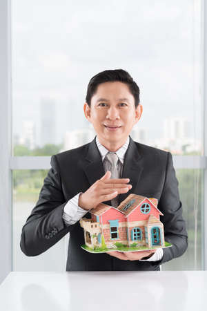 investment real state: Vertical portrait of a broker showing a house model for sale