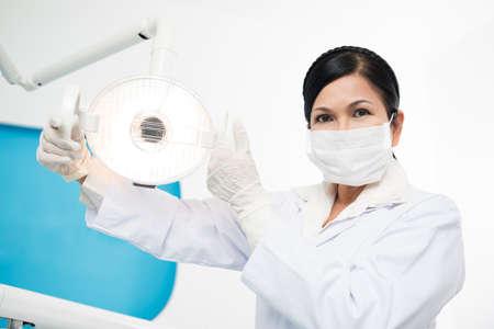 dentalcare: Portrait of a female dentist adjusting a dental lamp in the room