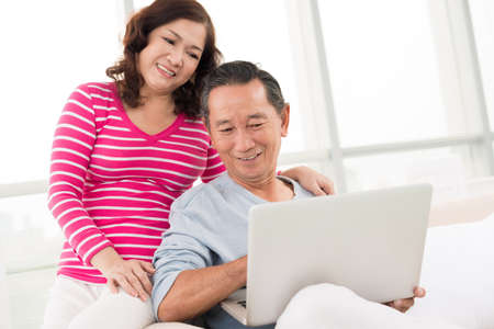 Senior showing something in computer to his wife