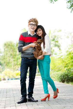 groomed: Portrait of a young couple with a dog in hands