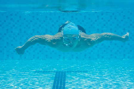 Image of a young guy swimming underwater  Stock Photo