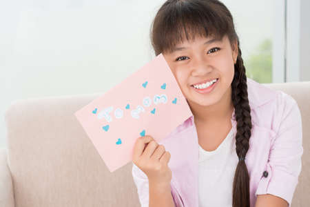 Portrait of a young girl holding postcard for mom Stock Photo