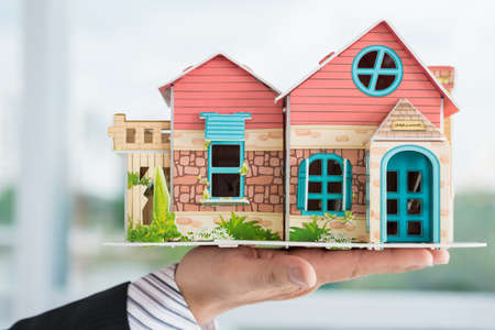 investment real state: Close-up of a male hand holding a house miniature Foto de archivo