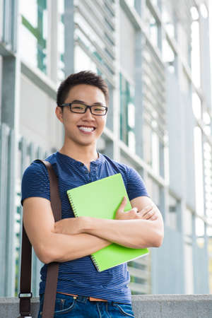 Vertical portrait of a cheerful male student standing outside