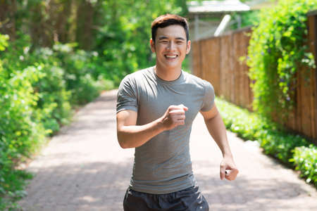 hacer footing: Image of a laughing jogger going in for sports outside Foto de archivo