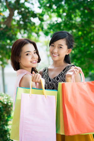 boasting: Vertical portrait of cheerful shopping friends holding bags with purchases