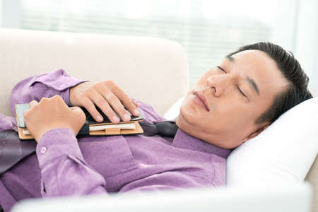 Close-up of a sleeping businessman with notepad in hands Stock Photo