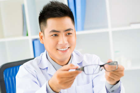 hyperopia: Portrait of a young male oculist giving eyeglasses