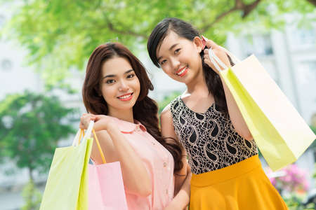 or spree: Portrait of two Asian girls enjoying their shopping weekend