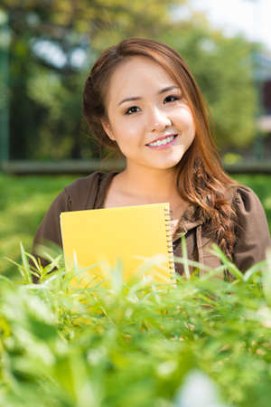 diligente: Vertical portrait of an attractive diligent female student outside
