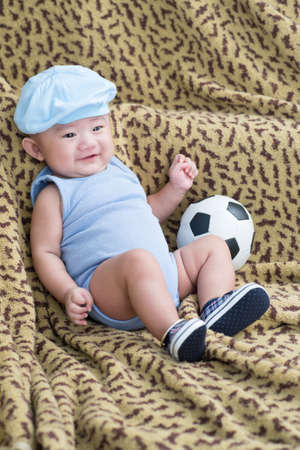 bedspread: Newborn with a soccer ball on the bedspread Stock Photo