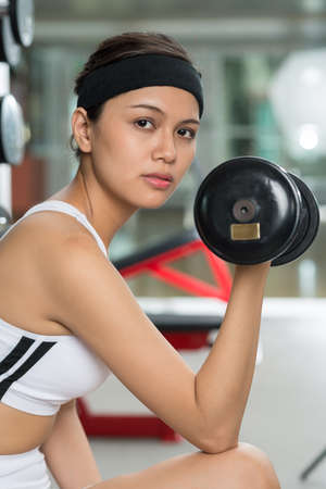 Vertical image of a determined girl building biceps
