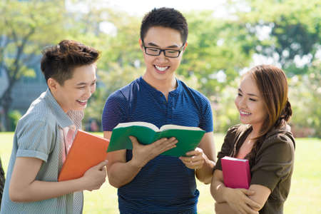 Image of students reading a joke in their book Stock Photo