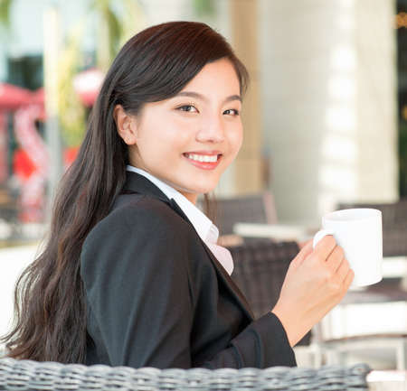 coffeecup: Young businesswoman with a coffee-cup at a cafe
