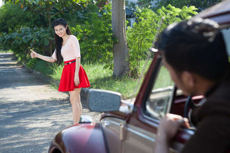 view to outside: Image of a girl stopping a car on the road