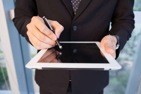 stylus: Close-up of male hands holding stylus pen and working on a tablet