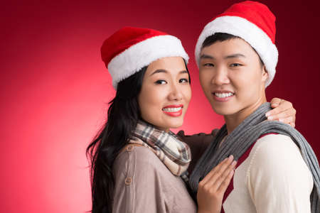 Copy-spaced portrait of an attractive young couple in Santa hats bonding and looking at camera