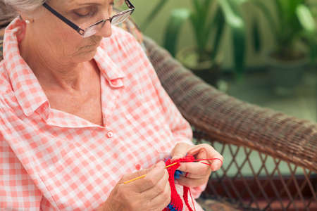 tiredness: Close-up of an elderly lady falling asleep while doing her knitwork