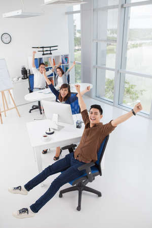 teamwork people: Vertical portrait of a cheerful business team with raised hands Stock Photo