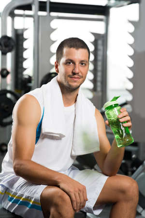 Portrait of a young man in gym drinking water Stock Photo