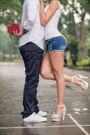 Cropped image of a young couple in-love where a boyfriend holding a giftbox for his girlfriend outside