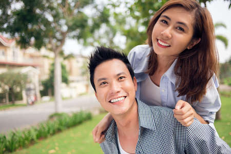 Image of a cheerful young couple piggybacking in the park Stock Photo