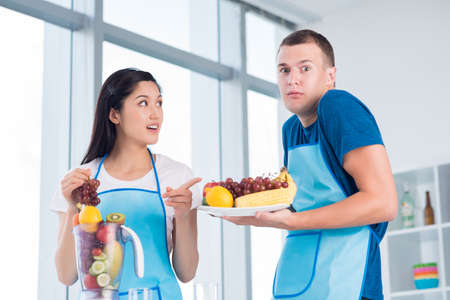bossy: Bossy young woman telling her husband to eat his lunch, a plate of fresh fruit and vegetables